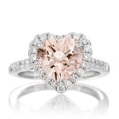 A Morganite ring with diamond accent in a white gold halo engagement setting. This diamond engagement ring features an 8x8 heart shape Morganite. A matching wedding band is available (sold separately), a straight diamond band which fits perfectly flush. Create an amazing bridal set by adding a