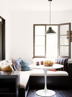 Bistro table with mixed pattern pillows and modern chandelier