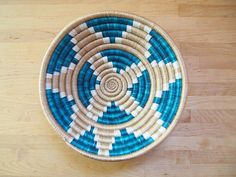 This sisal, woven bowl is handmade by our artisans in Gitarama, Rwanda in East Africa. The women grow their own sisal plants, extract the fibers, then hand-dye and weave them into these beautiful works of art. This sisal basket comes with a string attached to the back so that you can hang