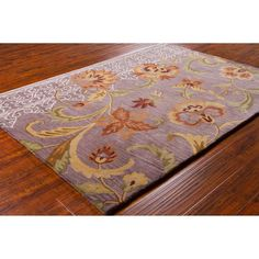 Add a coloful touch to your home decor with this floral style rug. This area rug is hand-tufed in India from fine quality imported wool. Area rug features a floral pattern in shades of brown, burgundy, gold, white and green against purple background.