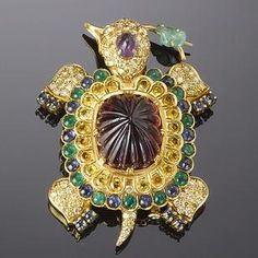A tourmaline and gem-set tortoise brooch, by Demner The fluted cabochon tourmaline shell with circular-cut yellow sapphire, cabochon emerald and blue sapphire decoration, the legs pavé-set with brilliant-cut diamonds, the head similarly set and with a cabochon amethyst crest, with a carved emerald stem in its mouth