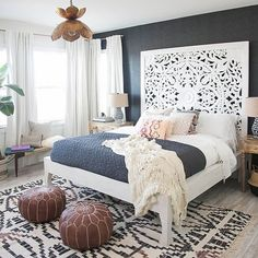 bedroom inspiration - white detailed headboard with blue coverlet pared with black wall and wine colored puffs