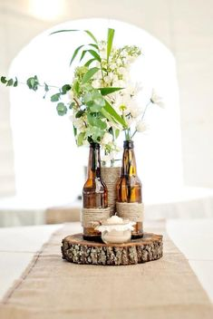 DIY wedding table centrepiece idea with wine bottles and flowers