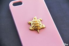 A hand-hammered 22kt gold plated turtle pendant laid on our pink hard shell case. Handmade to order!