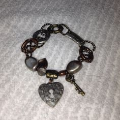 "Bracelet Silver, Gold, Copper colored bracelet. Has charms that say ""Open up the key to my heart"" ""I am loved"" and ""love laugh dream"" Accessories"