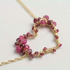 Another is my series of gem encrusted hearts--this one studded with rhodolite garnet and pink sapphires. Rich, deep pinks combine with gorgeous gold fill wire to form this asymetric heart on a delicate gold fill chain. The chain adjusts from 17 to 19 inches and the heart focal measure 1 1/4 inches across.  $158