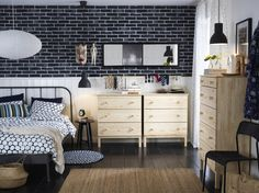 A medium sized bedroom furnished with a grey metal bed for two combined with chest of drawers in unfinished solid pine.