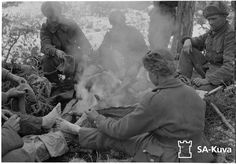"""Finnish Wartime Photograph Archive.  Drying the famous """"feetrags"""" around the campfire.  """"jalkarätti"""" in finnish."""