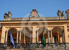 Photo made at the building that is the seat of the Town Hall of the city of Lodi in Lombardy (Italy). In the image we see the large veranda on the first floor.They also see four banners including the Italian and the European community.Over the roof, having as background the intense blue of the sky, we see a large central crest and two statues with a coat of arms smaller sides.