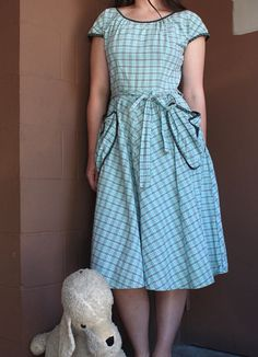 Vintage late 1940s powder blue plaid cotton wrap dress with black rick rack trim and heart shaped pockets! Perfect for a summer picnic or party! Ties at waist. Label: Brentwood MEASUREMENTS: Fits like a Large Bust: 38 Waist: From 28 up to 31 (because it wraps) Hips: Free Length: 43.5 CONDITION: Good vintage condition. Missing one little button at top back of neck. Freshly laundered and ready to wear. - - - - - - - - - - - - - - - -- - - - - - - Shop Home https://www.etsy.com&...