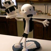 Greg Heffley, The Wimpy Kid. He stands 31 inches tall. His topsy-turvey cake is cake, his head is cake, and his backpack is cake. He is covered in modeling chocolate and fondant and is standing on one leg. The cake is vanilla buttermilk with orange creamsicle buttercream.  In the following pics you can see he is leaning back as if he is falling.