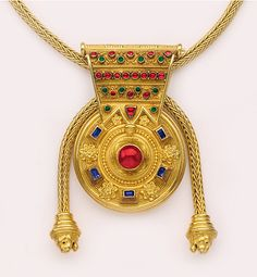 Ruby, sapphire, emerald, woven and granulated gold, Etruscan-revival bolla and necklace with retractable lion's head terminals. Castellani, London. The style is Etruscan revival with spun & woven high karat yellow gold necklace with slides to adjust the length & look of the necklace.   Etruscan revival refers to jewelry made in the Victorian era to mimic the jewelry archaeologists were unearthing in the ruins of Pompeii and Herculaneum.
