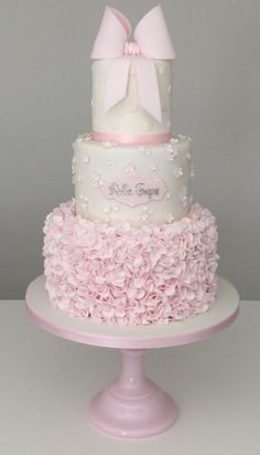 This three tier christening cake in delicate pink and white, featured ruffles, blossoms, polka dots and a touch of sparkle, topped with an icing bow