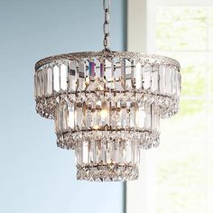 Add timeless elegance to your space with this clear crystal chandelier and its sparkling shade made from prisms and faceted squares.