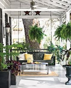 Here are a few of my favorite things: exposed ceiling beams, sturdy black swing with colorful pillows, lots of lush plants and a great looking table in front of the swing. Want everything on the porch! LJH