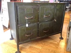 This is a unique vintage metal industrial cabinet. It has 4 pull out drawers and a lockable side door that has one shelf inside. It is a dark, army