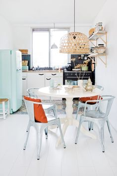 Cute little kitchen with light real fridge and matching chairs around kitchen tabke