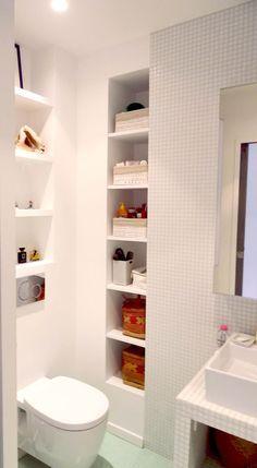 Banheiro pequeno com pastilhas brancas e nichos