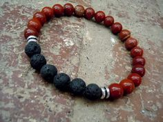 This wrist mala is a combination of black lava stone and brick-red jasper with silver accent beads. A meaningful wrist mala that is perfect for men and