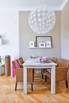 Týkový jídelní stůl byl záměrně patinován. Doplňují ho vyšší křesla z loupaného ratanu a polička s černobílými obrázky listů.