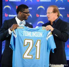 Former San Diego Chargers running back LaDainian Tomlinson, left, and Chargers president Dean Spanos hold up Tomlinson's #21 jersey
