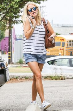 On-the-go: The mother-of-three flashed her tanned legs in denim shorts and a striped T-shirt when she arrived to the gym