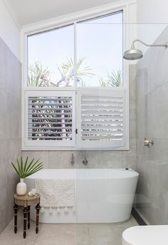 white freestanding bath in soft grey coastal bathroom with large window and walk in shower. #coastalbathroom #bathroomdesign #coastalhome #homebeautiful
