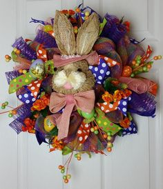 This wreath has a big bunny head, floral picks, wired ribbon, easter eggs, and silk flowers. W19 H 19