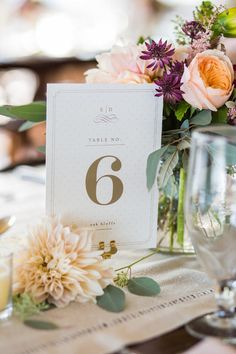 Elegant white + gold table number idea -  white cards with gold font + detailing displayed with floral centerpieces {Ashley Tilton Photography}