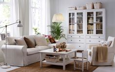 A bright living room with a two-seat sofa with chaise lounge, an armchair, a square-shaped coffee table and two glass-door cabinets with drawers, all in white.