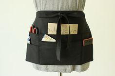 By popular request, a black half apron to meet your work wardrobe requirements. Free your hands and have everything where you need it, around your waist.  With this versatile half apron you can add pockets to any outfit.  #blackhalfapron #waitressapron #blackapron