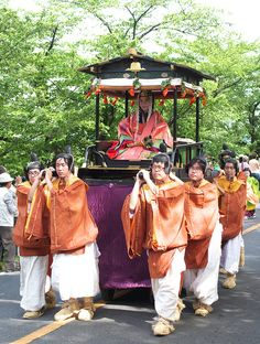 aoi-matsuri. A woman dressed in junihitoe being carried by men dressed in kariginu.