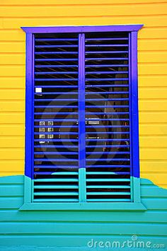 Colorful painted Caribbean window and shutters.