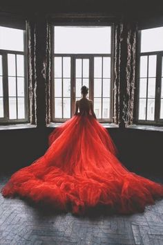 Woman wearing red gown looking out window