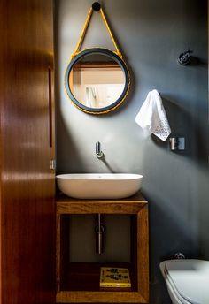 De madeira laqueada e corda náutica, o espelho é criação da moradora Marina Salles. Na parede, tinta Cinza Urbano, da Suvinil (Foto: Edu Castello/Editora Globo)