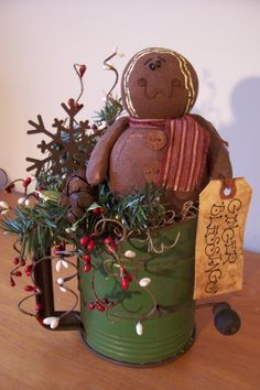 This sweet little ginger sits on a bed of spanish moss in a vintage Browmell Bee shifter that is embellished with pine, rusty jingle bells, pip berry sprigs, a large rusty snowflake and a grungy hang tag.  $24