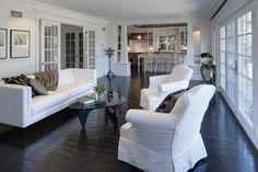 wide, dark wood floors / white walls and furniture / columns at opening from kitchen. crisp and clean.