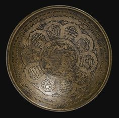 A CAST BRONZE MAGIC BOWL, NEAR EAST, 12TH/13TH CENTURY AD of shallow rounded form, the well engraved with an intertwining ten-pointed star, the cavetto with a pattern of calligraphic and figurative panels depicting a spider, a snake, a quadruped and two stylised human forms, the rim with two bands of inscriptions, the exterior with a narrow calligraphic frieze over alternating medallions and trapezoids containing inscriptions, the base with a calligraphic roundel