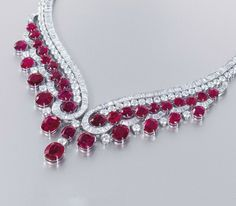 View: an impressive ruby and diamond necklace by Harry Winston of v-shaped design, the two baguette and brilliant-cut diamond rows suspending a fringe of oval and cushion-shaped rubies, mounted in platinum, cm long, in grey suede Harry Winston case. Red Jewelry, Luxury Jewelry, Gemstone Jewelry, Jewelery, Vintage Jewelry, Fine Jewelry, Lotus Jewelry, Ruby And Diamond Necklace, Ruby Necklace
