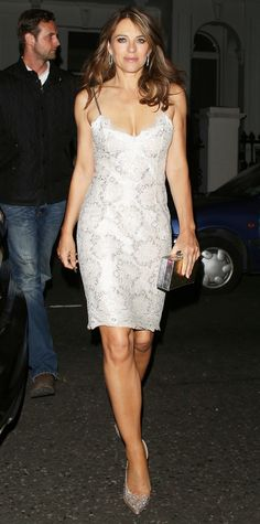 """Elizabeth Hurley was snapped arriving at the """"Shoes: Pleasure and Pain"""" exhibit in an embellished LWD, complete with diamond hoops, a sparkly box clutch, and, naturally, killer pumps."""