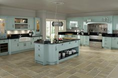 Duck egg blue is a wonderful choice for kitchen cupboards - and how amazing would it be to have a giant island like that to work on?!