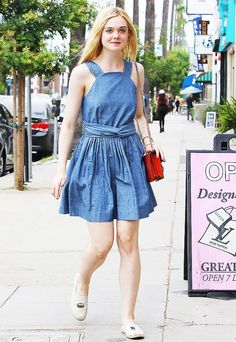 Elle Fanning wears a denim dress with espadrilles and a red bag