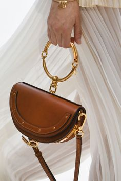 This SS2017 Chloé bag is exquisitely unique in its shape and gold ring-handle detailing. We want it...now.