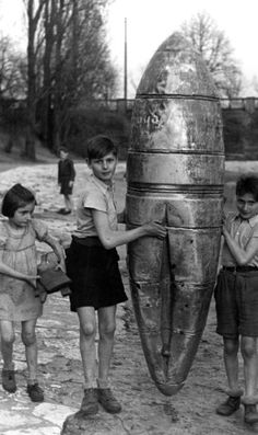 """Berlin children used the shell of this food drop """"bomb"""" to make an improvised kayak. In spite of terrible conditions, the photographs are ample evidence that life in Berlin went on. (kids will be kids, no matter what, but look at those too thin legs and arms!!)"""