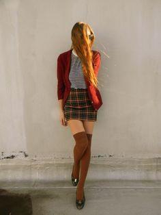 plaid skirt. striped shirt. sweater. knee high socks.