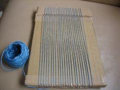 ダンボール織機 先日の裂き織り体験で、自宅でできる簡単裂き織りを教えていただきました。 ダンボールを利用した織機です。 ダンボールにカッターで切れ目を入れてタテ糸を張ります。