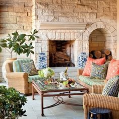 Vivid outdoor cushions add punch to the creamy tones of wicker and limestone on the porch of this renovated stucco villa.