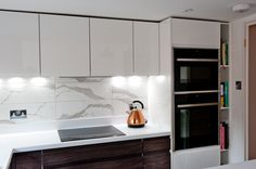 Gorgeous dark wood and marble design enhanced by down lighting and stylish interior details such as the copper kettle