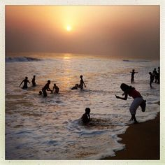 A woman photographs children playing in the ocean in Grand-Bassam, Ivory Coast on January 12, 2013. Just outside if Abidjan, Ivory Coast's commercial capital, Grabd-Bassam is a popular weekend destination for thousands of Ivorians. Photo by Peter DiCampo