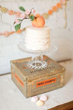 A hand-sculpted sugar peach serves as a cake topper